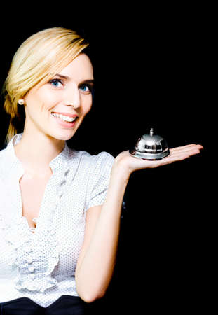 dutiful: Beautiful blonde lady with a lovely smile and attentive expression holding a silver service bell in her hand epitomising the old adage of Service With A Smile Stock Photo