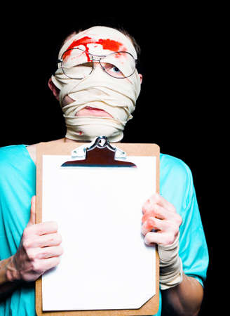 head injury: Person With Head Injury Wearing Hospital Clothing Holding Insurance Claim Clipboard Stock Photo