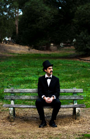 man sit: A Sorrowful Man In Mourning Dress Decides To Kill Some Time By Sitting On A Cemetery Park Bench