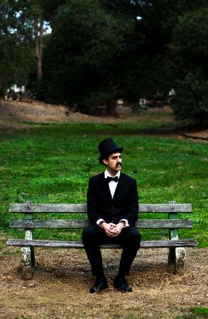 hombre con sombrero: Un hombre vestido de luto Dolorosa decide matar el tiempo Por sienta en un banco del parque cementerio