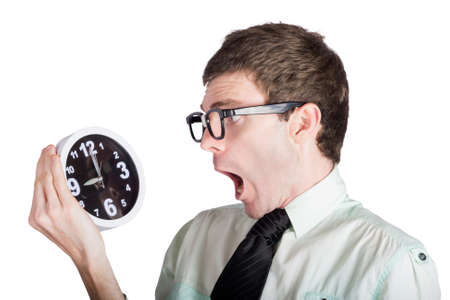 overslept: Shocked businessman looking at retro alarm clock, overdue concept on white background