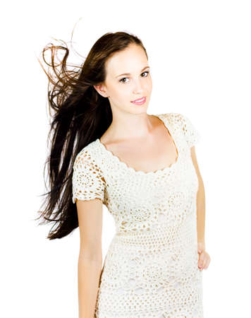 awry: Isolated Over White Photograph Of A Stunning Brunette Woman Standing Confidently With Hair Blowing In The Wind During A Glamour Fashion Model Photoshoot