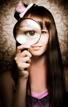 pert: Beautiful smiling female watching through magnifying glass Stock Photo