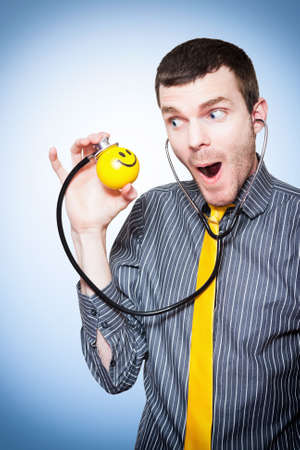 children's doctor: Fun Male Pediatrician Doctor Making Medicine Fun For Sick Kids While Checking The Health On A Childrens Smile Ball Stock Photo