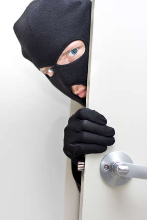 conman: A Masked Intruder Peers Around The Corner While Breaking In A Properties Front Door Stock Photo