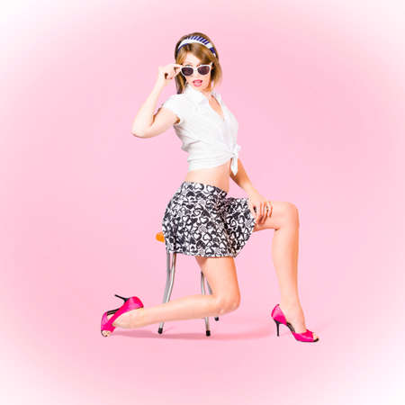 hair tied: Pink pop art photo of a beautiful pinup girl strutting a beauty pose wearing 1950 style mini skirt and tied shirt with pink high heel shoes and girly accessories. Makeup and hairstyle concept Stock Photo