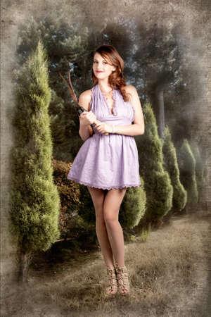 femme brune sexy: Femme élégante dans le jardin tenant sécateurs dans une mini robe violette
