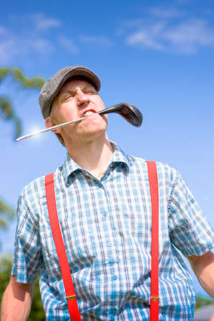 grimaces: Golfer Grimaces With An Evil Expression While Holding His Broken Golf Club In His Mouth In A Funny Game Over Golfing Conceptual