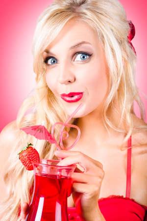 temptress: Stunning blond female drinking strawberry nightclub cocktail through heart shape straw. Cocktail love