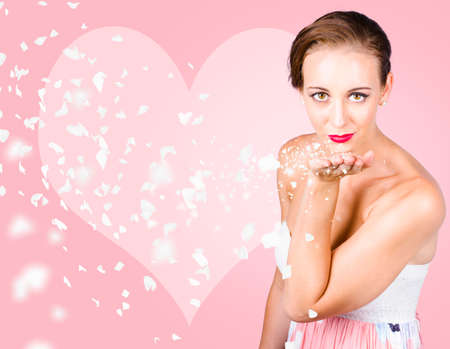 feel affection: Lovely brunette woman blowing magic love petals into the air with glamorous style. Love is in the air