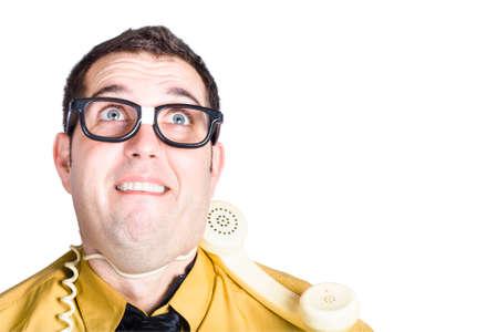 agotado: Retrato de hombre de negocios en camisa amarilla y corbata oscura con el cable del teléfono alrededor del cuello agotado, trabajando bajo estrés aislado sobre fondo blanco Foto de archivo