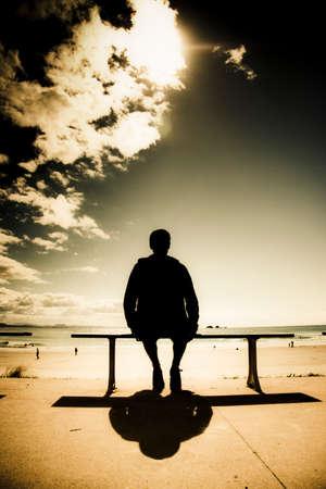 seated man: Foto creativa al aire libre de un hombre joven en silueta sentada al sol en un parque banco en una playa australiana, fotografía tomada la playa de Wategos, Byron Bay Australia