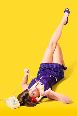 50s fashion: Old 50s photo of a retro pinup girl flirting on phone in full length wearing classic fashion accessories with polkadot dress and purple heels on yellow background
