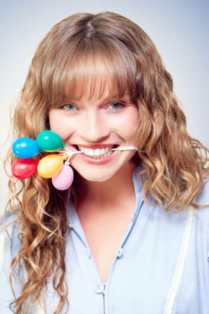 tantalising: Fun party girl holding a bunch of colourful miniature toy balloons in her mouth while grinning mischievously at the camera