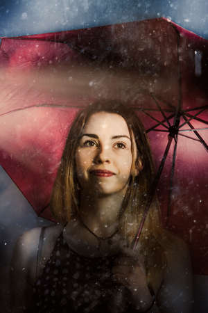 resilience: Creative fine art of a beautiful woman walking unhindered through the pouring rain with umbrella. Resilient in storms by positive thinking Stock Photo