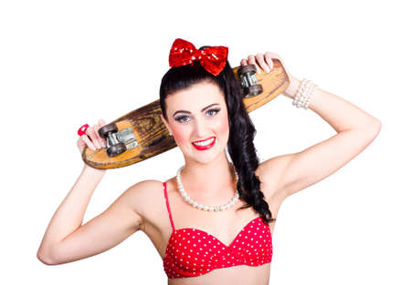 50s fashion: Sporty female holding skateboard deck in punk glam fashion. 50s skate subculture Stock Photo