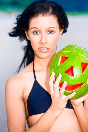 enquiring: Young Woman At The Beach With Look Of Confusion While Holding A Watermelon With Carved Smiling Face Symbolizing Having Mixed Feelings That Do Not Always Match Surroundings