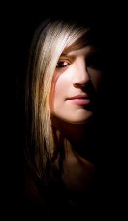 appearing: Portrait Of Attractive Young Blond Woman With Long Hair Appearing Out Of Black Shadowy Background