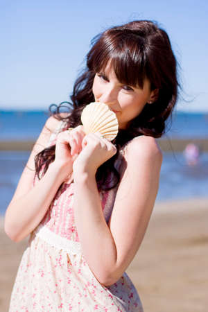 enjoyment: Attractive Smiling Young Woman Holds A Shell Up In A Happy Expression While On Vacation At The Beach