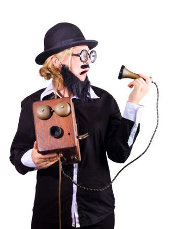 black rimmed: Funny bearded woman in wide rimmed spectacles spectacles, black homburg trilby hat and jacket holding antique phone isolated on white
