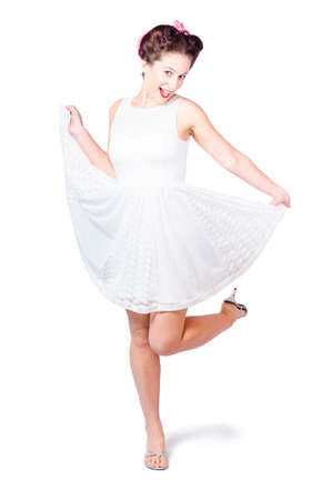 50s fashion: Young happy 50s pinup woman in white dress dancing with old fashion hair style and make-up in full length retro portrait