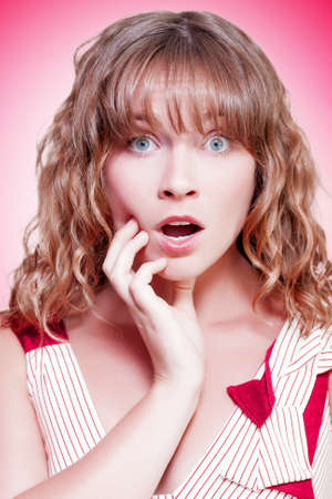 appalled: Woman looking shocked and appalled with a dropped jaw and wide eyes as she stares straight into the lens on a pink studio background with colour gradient