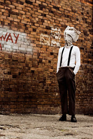 bewilder: Vintage Man Stands In A Streets Dark Back Alley Lost In The Mystery Of Yesteryear With A Vintage Newspaper Covering His Face