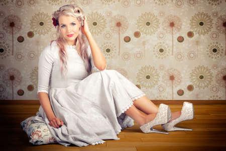 ojos azules: Fotografía de una mujer hermosa de la vendimia Rubia Con arquetípica años cincuenta peinado y ropa de lujo Sentado en el suelo de madera en una representación de la manera del estilo clásico