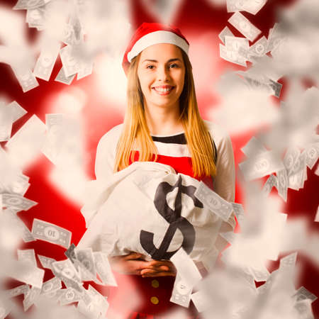 Christmas business concept on a smiling santa woman celebrating a money bag win under abstract opulence. X-mas bonus