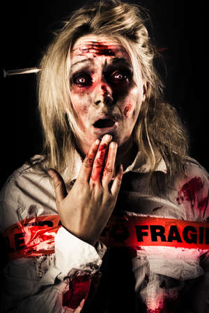 Evil zombie woman expressing fear and shock horror when awakening in a morgue wrapped in fragile postage tape, NDE or near death experience concept on black background Stock Photo