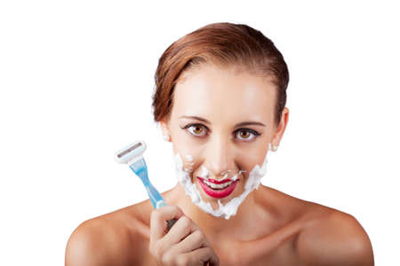 battle of the sexes: Young short-haired caucasian woman using mans razor to shave face in a comical beauty products conceptual over white