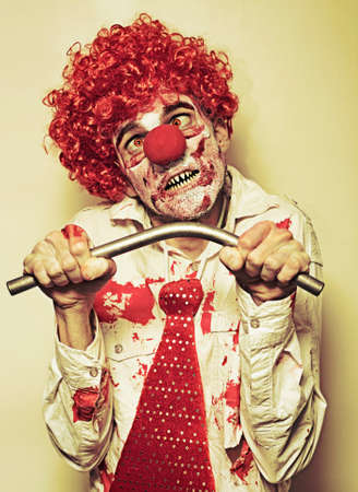 possessed: Retro Possessed Male Horror Clown Bending A Metal Pole With Bare Hands In A Concept Of Supernatural Strength And Endurance