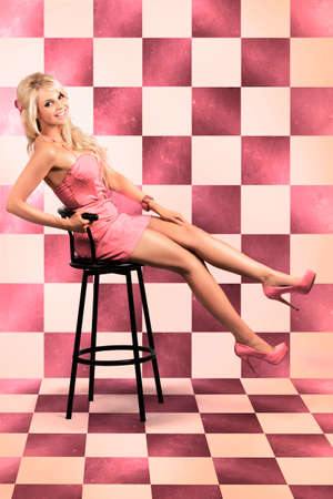 barbie: Beautiful Retro Lady In Pink Rockabilly Dress Sitting On Bar Stool Inside Retro Diner In A Depiction Of 60s American Pin Up Culture Stock Photo