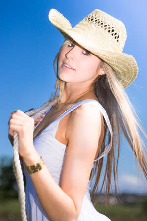 Half Body Portrait Of Attractive Young Woman With Rope And Cowboy Hat In Countryside Blue Sky Background