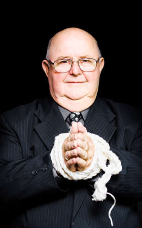 freewill: A sympathetic senior male business person stands with his hands tied by a rope unable to offer assistance or have freedom of choice due to bureaucracy and red tape, metaphor concept My hands are tied