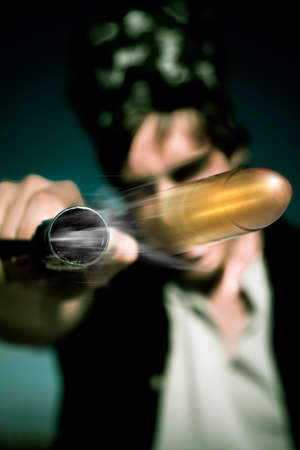 shot: Action Shot Of A Flying Bullet Shooting Out Of The End Of A Gun Held By A Evil Robber Man During A Night Home Burglary In A Break And Enter House Invasion Stock Photo
