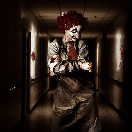 Spooky dark horror portrait of a female doctor clown posing in a shady hospital corridor. Theatre nightmare Stock Photo