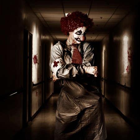 clown cirque: Spooky portrait d'horreur sombre d'un clown de la femme m�decin posant dans un couloir de l'h�pital ombrag�. Th��tre cauchemar