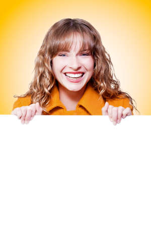 mirth: Vibrant young woman laughing merrily while holding a blank white sign for your advertising and text on a colourful orange studio background with gradient Stock Photo