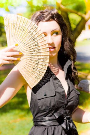 damn: Damn Hot Brunette Woman Looking Off-Camera Cools Herself Down With An Asian Fan While Standing In A Temperate Warm And Humid Summer Location