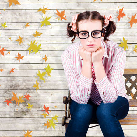 introvert: Sad Introvert Businesswoman Sulking In A State Of Depression While Sitting On An Autumn Park Bench Outdoors In A Depiction Of A Business Networking Crisis Stock Photo