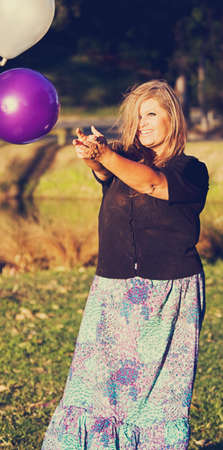 liberate: Woman Lets Go Of Party Balloons In A Joyful Sweet Release