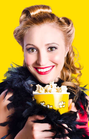 thespian: Broadway showgirl holding box of theatre popcorn during cabaret performance. Yellow background Stock Photo