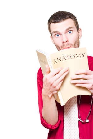 impish: Humorous Healthcare Image Of A Young Medical Intern Student Studying Anatomy Textbook With A Expression Of Surprise