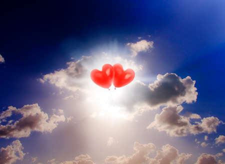 romance sky: Sky Bound Romance Picture Of Two Red Floating Love Heart Balloons Touching In Front Of Beautiful Cloud Sunset Stock Photo