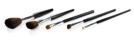 angled: Set Of Makeup Brushes consisting of large powder, angled blush bronzer, eyeshadow, angled shadow contour and angled liner brush arranged in a row on white
