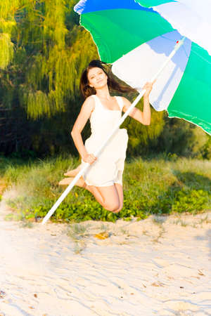 mini umbrella: Beautiful Young Caucasian Woman With Smiling Facial Expression Jumping Bounding And Leaping On The Sand Of A Tropical Island Beach