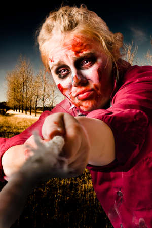 relentless: Female zombie pulling on a tug of war rope with cuts and bruises in a show of courage, strength and resilience. Determined spirit Stock Photo