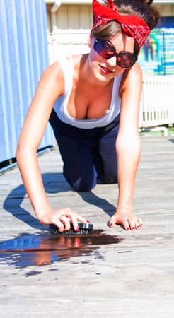 retro housewife: Cross Processed Vintage Image Of A Sexy Retro Housewife Scrubbing And Cleaning A Wooden Deck With Water Outdoors Wearing Bandana A Low Cut Top