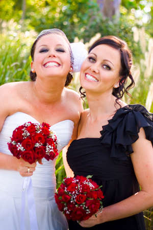 glee: A Bride Wearing A Wedding Dress Smiling With Glee And Posing With Her Happy Maid-Of-Honor Wearing Black Dress And Showing Their Friendship And Care For One Another Against Grassy Outdoor Background
